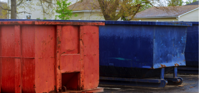 red and blue dumpster in the parking lot